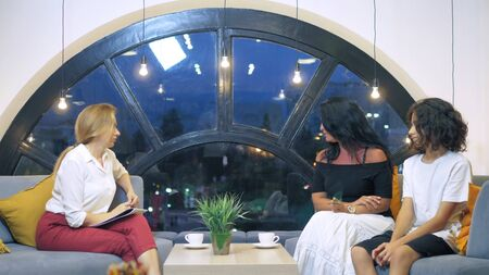 Family counseling and socialization issues in a big city concept. A woman psychologist consults a woman and her teenage son in an office with a large beautiful window from which the lights of the modern city are visible.