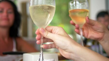 close-up. people clink glasses of wine at a table at a friendly or family dinner