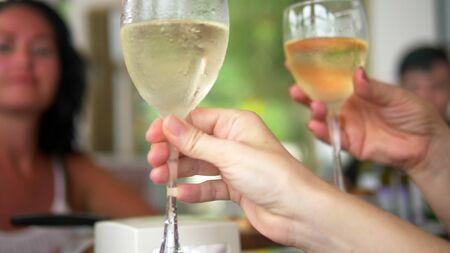 Nahaufnahme. Leute stoßen bei einem freundlichen Abendessen oder Familienessen an einem Tisch mit einem Glas Wein an