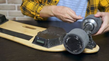 close-up.Man hands who repair a broken electric skateboard. unscrews the wheels.