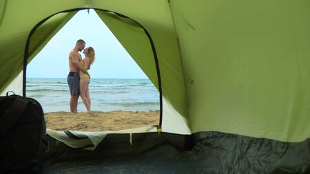 Camping concept by the sea. view from the tent, a couple man and woman cuddling Reklamní fotografie - 131877529