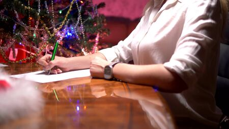 business woman sits at a table near a decorated Christmas tree and writes a Christmas letter to Santa Claus.