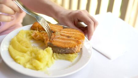 close-up. someone eating red fish steak with mashed potatoes with a fork. Фото со стока