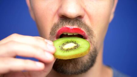 close-up. funny image of a bearded man with lip make-up holding a kiwi in his mouth. Banco de Imagens