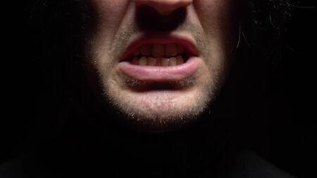 fermer. bouche masculine avec des dents tordues criant. Fond noir. Banque d'images