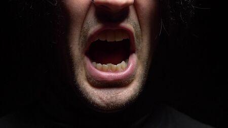 fermer. bouche masculine avec des dents tordues criant. Fond noir.