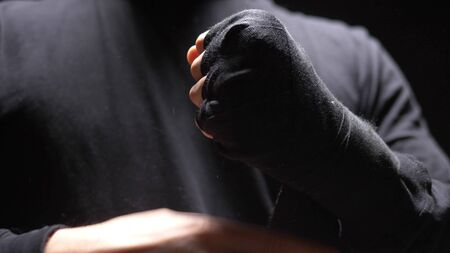 closeup. male hands wrapped around a black elastic bandage on hand.