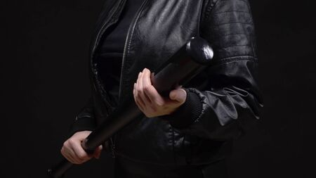 closeup. female hands holding a baseball bat on black background