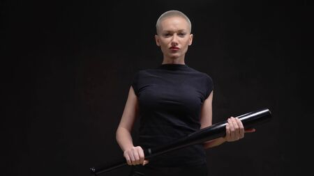 beautiful short haired blond woman with a baseball bat on black background Standard-Bild - 135467602