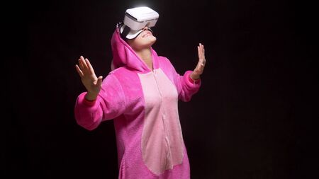 girl in pink pajamas kigurumi in VR glasses on a black background. pajama party