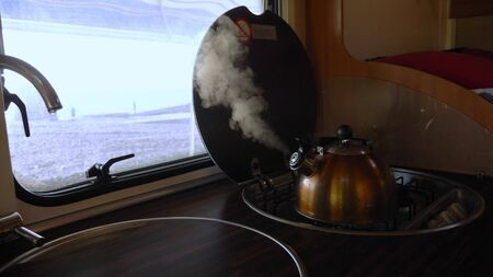 the kettle boils on the stove in the motorhome. the steam from the kettle.