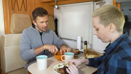 man and woman eat the meat at the table in the motorhome