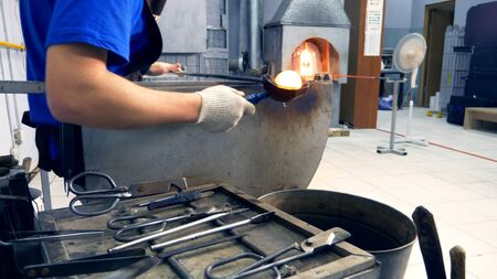 glassblower. manufacturer of glass products. man heats glass in a furnace Stock Photo