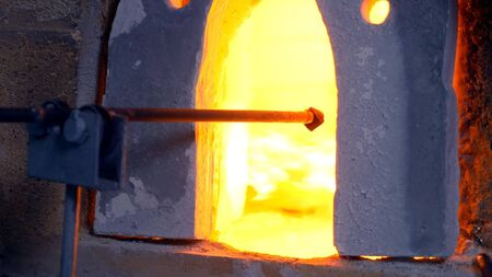 glassblower. manufacturer of glass products. man heats glass in a furnace Фото со стока