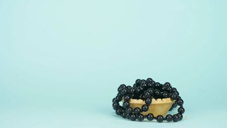 fashion art. minimalism. the black beads fall into the tartlet. blue background Banco de Imagens