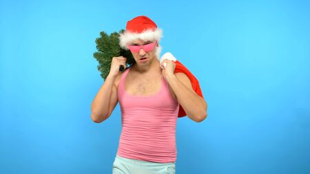 Playful handsome man in a pink T-shirt with fashionable stylish New Year's accessories, in fashionable pink glasses, Merry Christmas and Happy New Year Фото со стока