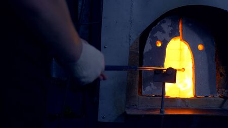 glassblower. manufacturer of glass products. man heats glass in a furnace Imagens