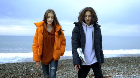 teenagers throw plastic garbage on the beach in the fall. Reklamní fotografie