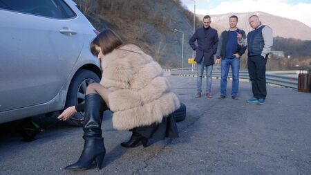 a girl changes a wheel on a car, while men look from the side