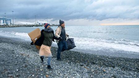 Feliz pareja de personas sin hogar, un hombre y una mujer corriendo en la playa