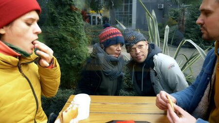 a couple of homeless men and women ask for food from visitors to a street cafe Zdjęcie Seryjne