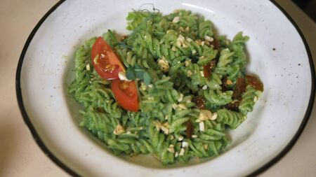 fashionable design food. vegetarian pasta with green sauce and cashew nuts