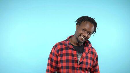 portrait of a stylish handsome African guy on blue background