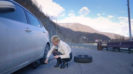 beautiful girl changing the wheel of a car parked on the roadside Archivio Fotografico