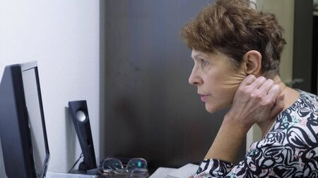 elderly woman at the computer sits at a table in the home office