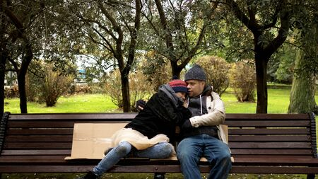 a homeless couple, a man and woman on a bench in a city park