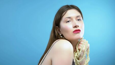 beautiful young girl with pearls and earrings on a blue background