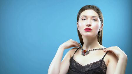 beautiful young girl wears a necklace. blue background