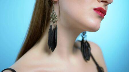 portrait of a beautiful girl. blue background. the girl wears earrings Zdjęcie Seryjne