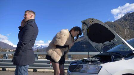 humor. woman looks under the bumper of a car. man talking on the phone Zdjęcie Seryjne