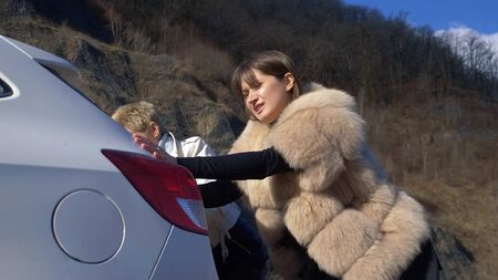 two beautiful girls push the broken car on the road. a man sits behind the wheel