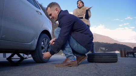 a man changes a wheel on a car, a girl is dissatisfied scolds him