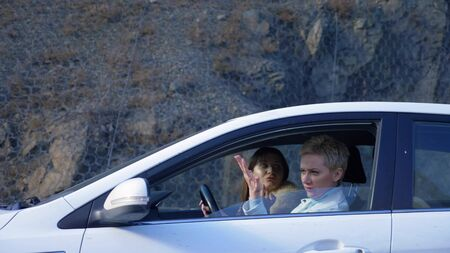 two girls ride in the car and fighting. fight friends or lesbians Standard-Bild