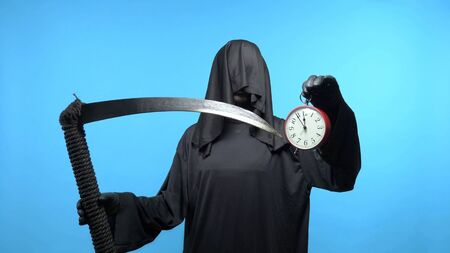 A man in a death suit with a scythe, shows a clock. blue background