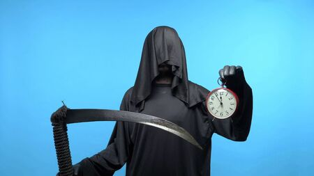 A man in a death suit with a scythe, shows a clock. blue background Imagens