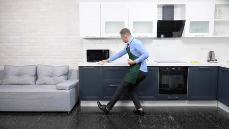 handsome man in an apron and tie. cleans up the kitchen in the apartment Zdjęcie Seryjne