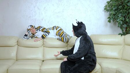 metaphor, humor. husband and wife costumes cats and dogs fighting on the couch. Stock Photo