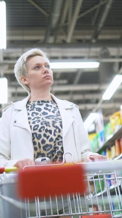 vertical shot. portrait of stylish woman in the supermarket with a grocery cart
