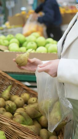 vertical shot. closeup of hands. a woman chooses pears in the supermarket