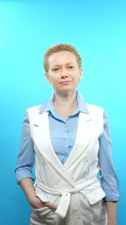 vertical shot. blonde woman without makeup on a blue background.