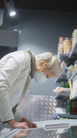 vertical shot. blond woman in medical mask at the grocery store. pandemic
