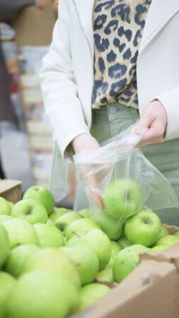 vertical shot. closeup of hands. woman picks green apples in the supermarket
