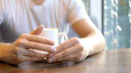 closeup. the man wears a wedding ring, sitting in a cafe. Zdjęcie Seryjne