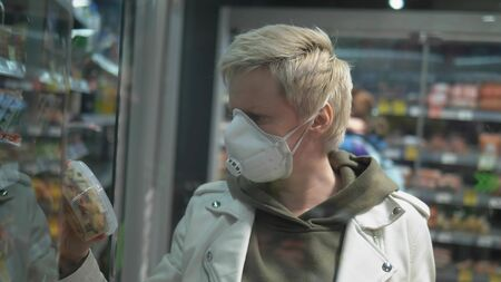 short haired blond woman in medical mask at the grocery store. pandemic