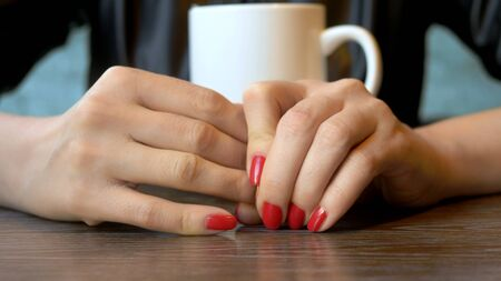 closeup. the woman takes off her wedding ring sitting in a cafe