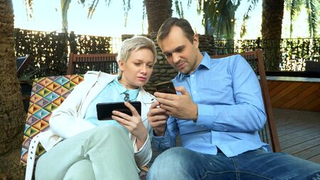 couple man and woman use their smartphones sitting in a cafe outdoor Zdjęcie Seryjne